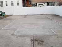 Outline of filled in pool is visible in existing concrete to be installed with a royal blue and ice blue basketball court, goal system, and containment fence in Revere Beach, MA.