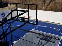 Royal blue and ice blue basketball court in Revere, MA. This was installed on existing concrete that included a cap on a filled in pool. Viewed from adjacent deck behind goal system.