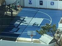 Royal blue and ice blue basketball court in Revere, MA. This was installed on existing concrete that included a cap on a filled in pool. Viewed from a tall adjacent building for an almost overhead shot ny the court owner.