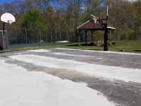 Asphalt basketball court being prepped for resurfacing at Seekonk Swimming and Tennis Club in Seekonk, MA. This shows where low spots have been filled and the surface leveled and smoothed.