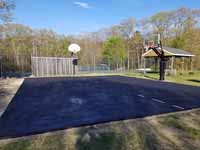 Asphalt basketball court at end of prep for resurfacing at Seekonk Swimming and Tennis Club in Seekonk, MA. This shows the trimmed, filled and leveled surface after sealcoating has been applied to repel water and extend life.