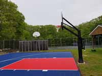 Resurfaced asphalt basketball court in blue and red at Seekonk Swimming and Tennis Club in Seekonk, MA.