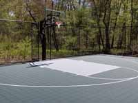 HBackyard basketball court, in Versacourt slate green and titanium, in Stow, MA. This is a similar view to the before picture showing the barren spot for the proposed court, with an overview of the finished product.
