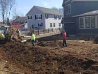 Photo from installation of a sand and emerald green residential backyard basketball court in Swampscott, MA. Before anything else, the way must be cleared for a lasting base. In this one, top soil and especially organic materials are being removed from the planned court site.
