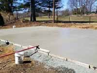 Photo from installation of a sand and emerald green residential backyard basketball court in Swampscott, MA. Last step is to pour and smooth cement that will become a reinforced concrete base for the court tiles.