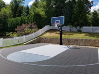 Residential backyard basketball court in charcoal and titanium colors in Wellesley, MA.