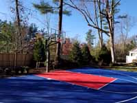 Navy blue and red residential basketball court on asphalt surface in Wellesley, MA.