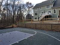 Graphite and titanium residential backyard basketball court in Westford, MA, with retaining wall, gated containment fence, and wood rail fence.