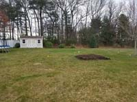 Existing lawn that will become the site of a dark green and grey backyard basketball court in Agawam, MA.
