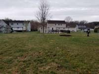 Patch of  back yard that will become a dark green and grey backyard basketball court in Agawam, MA.