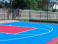 Light blue and red residential basketball goal system, containment fence and court surface in Halifax, MA.