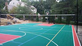 Backyard basketball court plus tennis and volleyball in Pembroke, MA, featuring green and red Versacourt tiles.