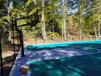 Side view of goal system in end zone of large emerald green and titanium backyard basketball court in Bolton, MA.