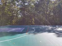 Part of an end zone of large emerald green and titanium backyard basketball court in Bolton, MA, complete with sunbows.