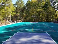 View of most of large emerald green and titanium backyard basketball court in Bolton, MA, still under last of construction. Besides full-featured basketball court and hoops, plus containment fencing, middle of court is lined for pickleball, to be played with a portable net not shown.