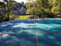 View of much of large emerald green and titanium backyard basketball court in Bolton, MA, with orange pickleball lines, for use with portable net, in foreground.