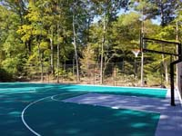 Angled view from corner beside one hoop out at part of large emerald green and titanium backyard basketball court in Bolton, MA.