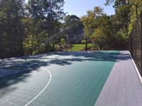 Sun-soaked view of most of length of large emerald green and titanium backyard basketball court in Bolton, MA.