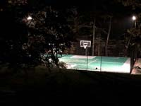 Night time view of large emerald green and titanium backyard basketball court in Bolton, MA, lit by optional LED lighting system for play after hours.