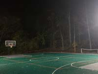 Large emerald green and titanium backyard basketball court in Bolton, MA, lit by energy efficient overhead LED lighting system for night play.