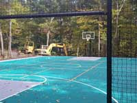 View through gateway in fence around large emerald green and titanium backyard basketball court in Bolton, MA.