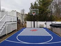 Blue and grey small backyard basketball court with custom red H logo in Braintree, MA.