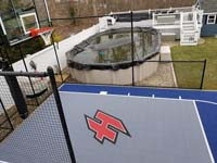Custom red H logo on small blue and grey backyard basketball court sport surface with accessories in Braintree, MA, adjacent to existing pool.