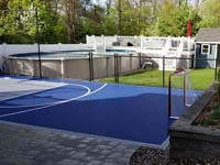 View from patio across small blue and grey basketball court, toward backyard and existing pool existing pool in Braintree, MA.