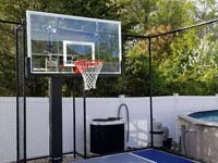 Closeup of hoop and rebound fence for small blue and grey basketball court by existing pool in Braintree, MA.