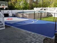 Outstanding blue court in a small backyard space, featuring a titanium colored key and a custom stylized red H logo, installed for a happy customer in Braintree, MA.