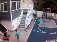 Kids playing on small blue and grey basketball court, with optional hockey net and custom logo, in Braintree, MA.