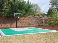 Green and silver backyard basketball court in Bridgewater, MA.