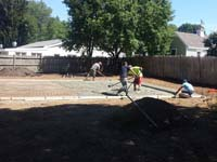 Pouring and working cement for sturdy concrete backyard basketball court base in Canton, MA.