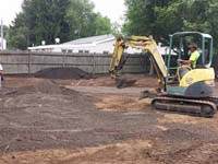 Personal basketball court construction preliminaries in Canton, MA, creating a packed gravel underlay for the subsequnt concrete base.