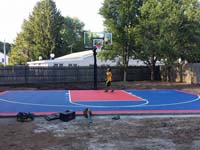 Lucky kid trying out mostly completed backyard basketball court in Canton, MA.