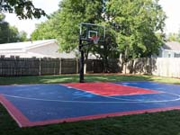 Small red and blue backyard basketball court in Canton, MA.