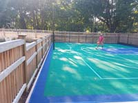 This emerald green and royal blue home basketball court is one you might find in Carlisle, MA or a yard like yours.