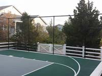Slate green and titanium tiled basketball court with fencing in Plymouth, MA.