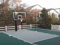 Home basketball court in Plymouth, M, featuring goal system, tall fence, and Versacourt tile surface in green and titanium. Whatever your sport, you could have a court surface and accessories of your own in Dover, Bedford, Cambridge, Acton or Burlington.