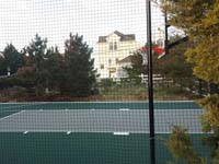 View through rebounder fence at green and gray basketball court in Plymouth, MA.