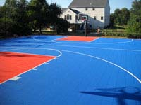Near professional size home basketball court in Bellingham, MA, with royal blue and orange colors.