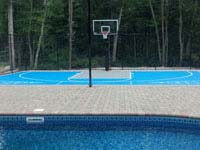 Basketball and shuffleboard game court in light blue and titanium tiles on concrete foundation integrated with a pool and deck in Wareham, MA.