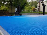 Closeup view of Versacourt royal blue game outdoor tile used on a basketball court in Douglas, MA, which also features a titanium colored key and border, with white lines.