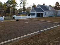 Form and rebar for reinforced concrete base for construction of dark green basketball court in Duxbury, MA.