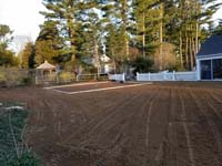 Prep work for construction of dark green basketball court in Duxbury, MA, in context of owner's wider backyard landscaping.