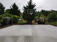Concrete base, and hoop already installed, ready to court a beige and green court surface in Easton, MA.