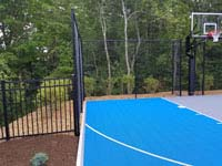 Blue and gray residential basketball court in Easton, MA, focused on left side of court, fence and goal.