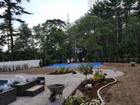 Kids on blue and gray residential basketball court in Easton, MA, with landscaping by Evergreen still in progress.