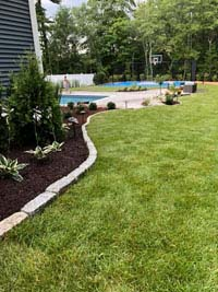 Distance view of blue and gray residential basketball court in Easton, MA, highlighting the partner work by Evergreen Landscaping.