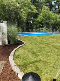 Blue and gray residential basketball court in Easton, MA, viewed from left side of yard, highlighting landscaping by Evergreen.